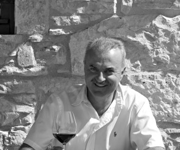 Marino Markežić holding a glass of red wine on the terrace of Kabola winery